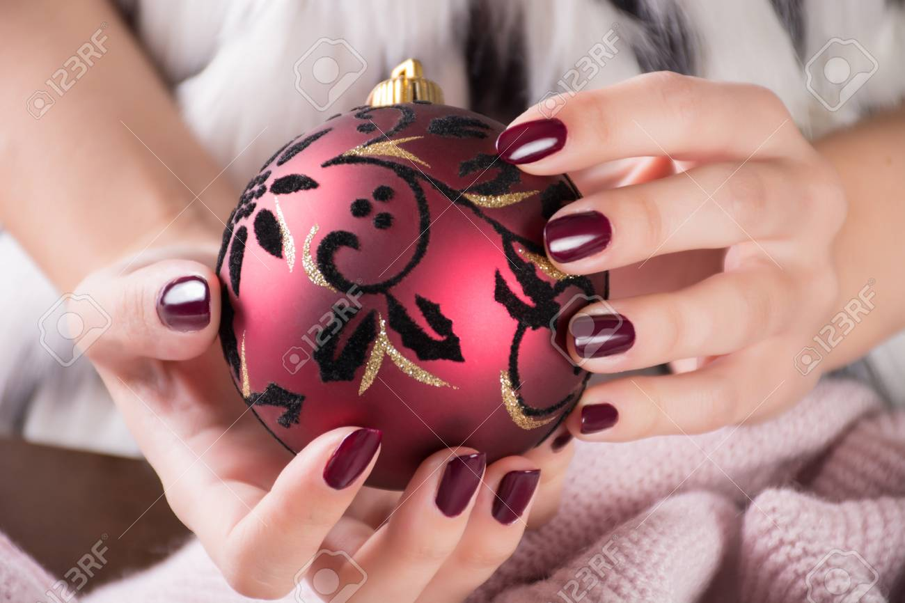 Girl With Red Wine Color Nails Polish Gel And Holding Christmas
