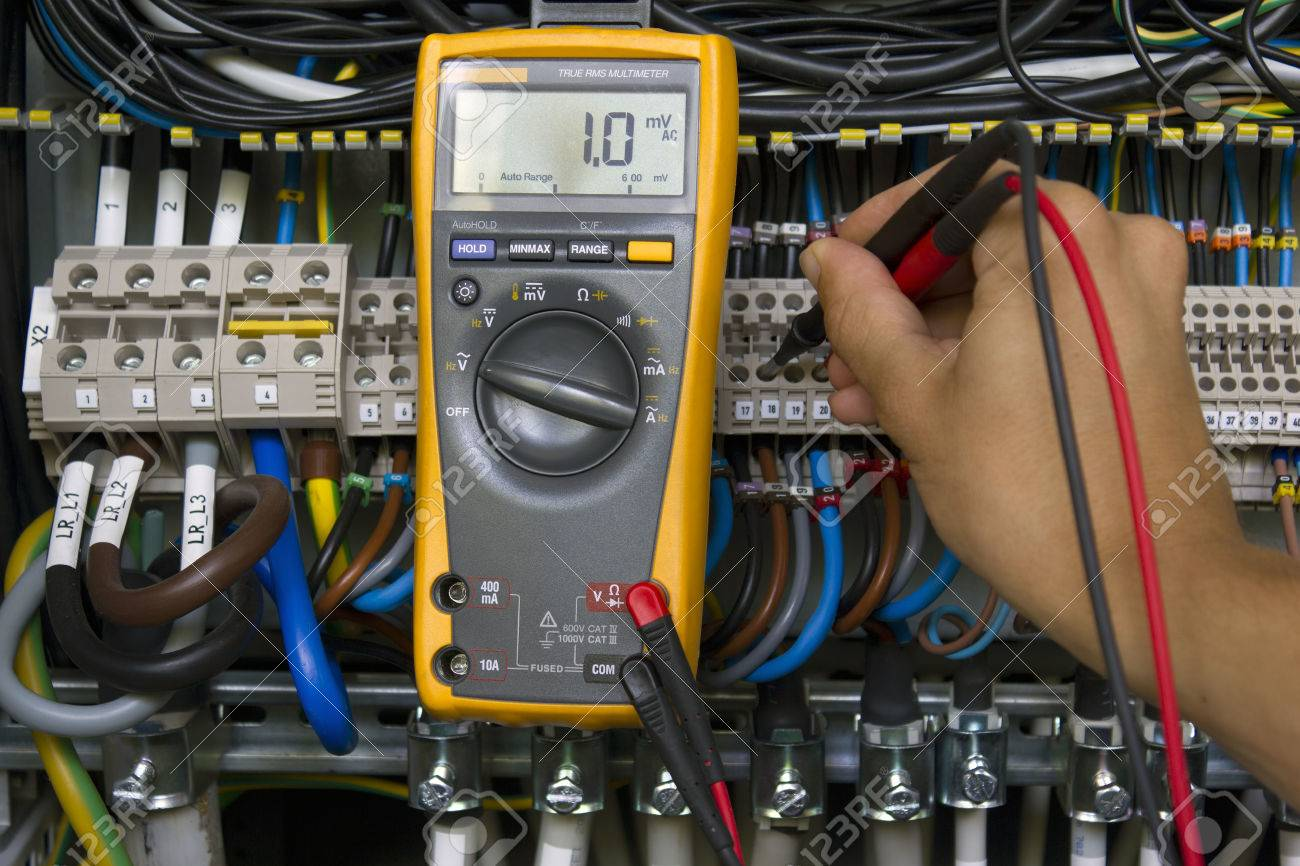 Electrical Panels 101 Engineer Stock Photos Royalty Free Electrician Performing Voltage Measurements With Multimeter