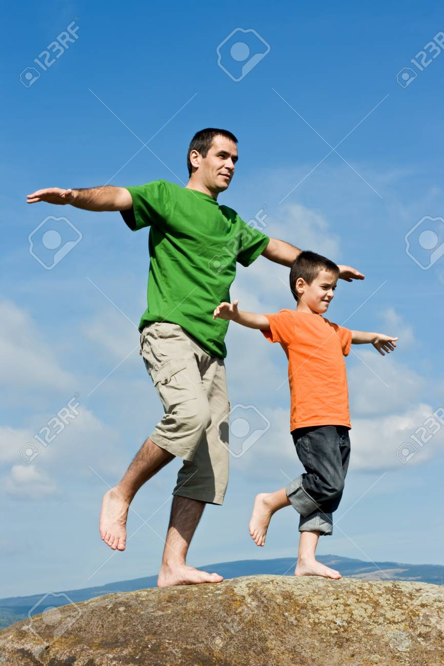 Father and his happy son staying on the stone with lifted legs and balancing Stock Photo - 16925857