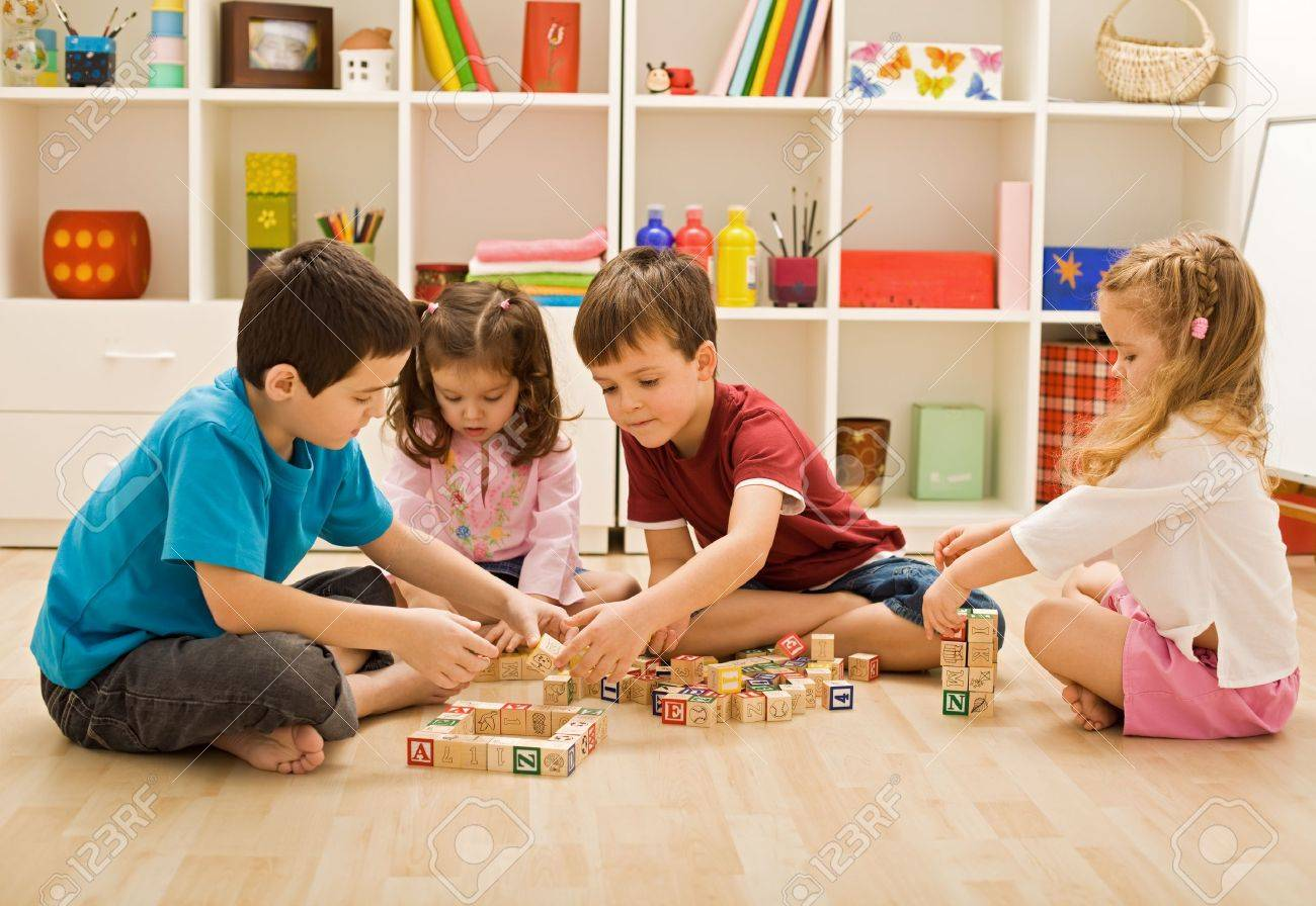 Children playing with blocks on the floor - focus on the boy's face Stock Photo - 16925874