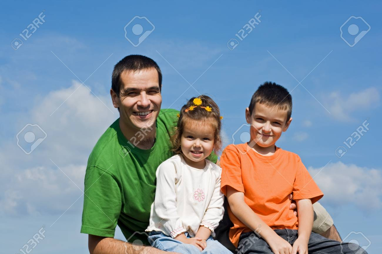 Father and his happy children sitting on the stone Stock Photo - 17218756