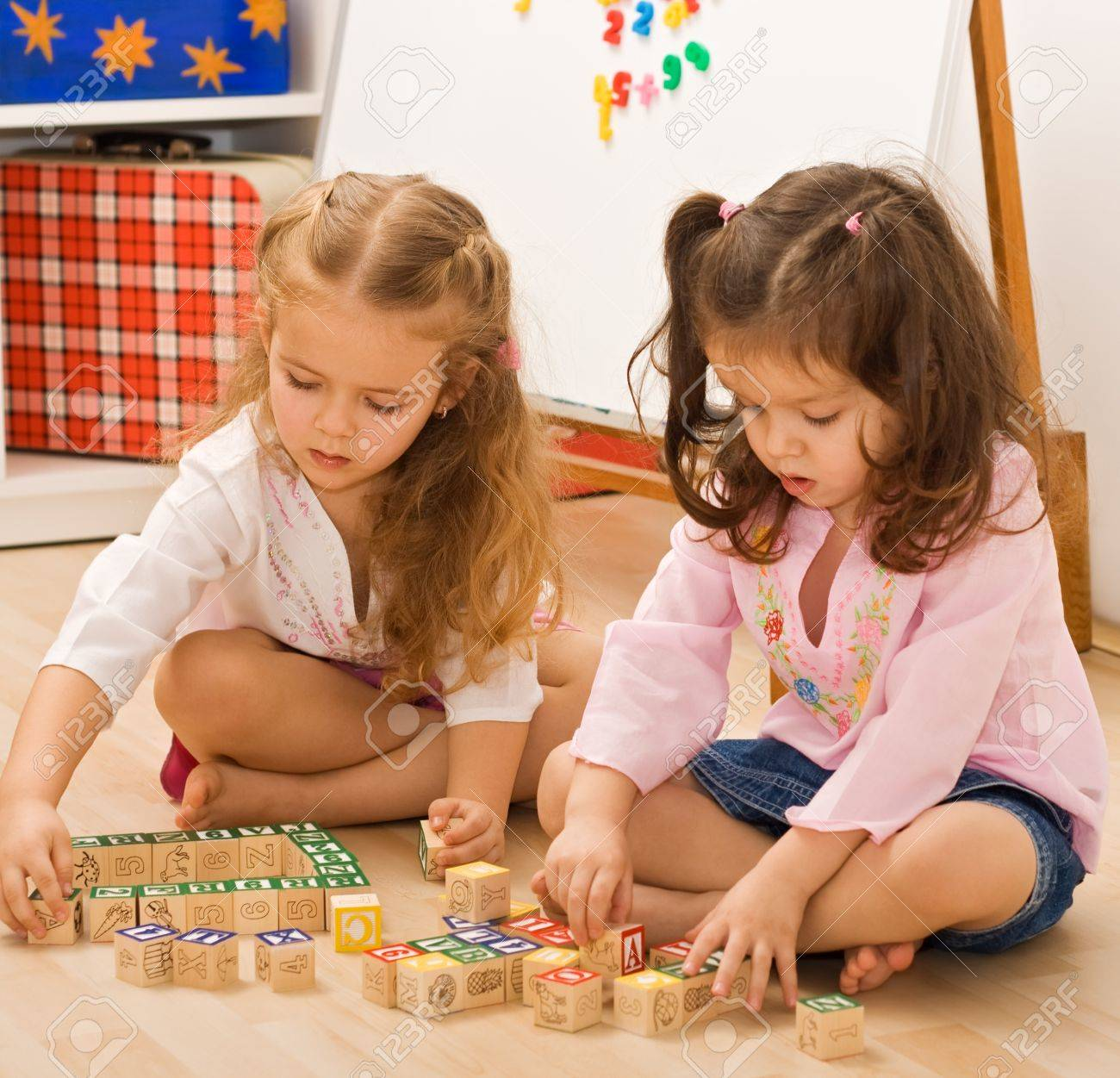 Little girls playing with blocks on the floor Stock Photo - 17218753