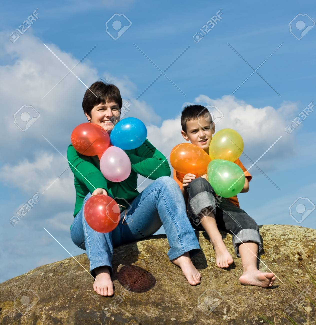 Beautiful woman and her son sitting on the stone with balloons in their hands Stock Photo - 17505009