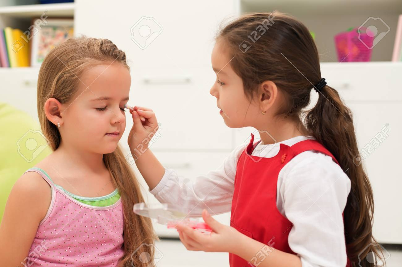 Little girl doing make-up of her girlfriend Stock Photo - 17566119