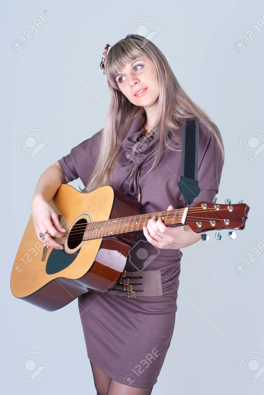 A young girl stands with a guitar in hands Stock Photo - 13755172