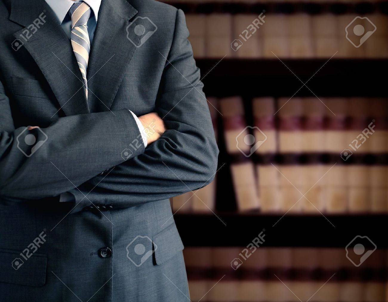 Businessman wearing a suit in front of a bookcase Stock Photo - 11696462