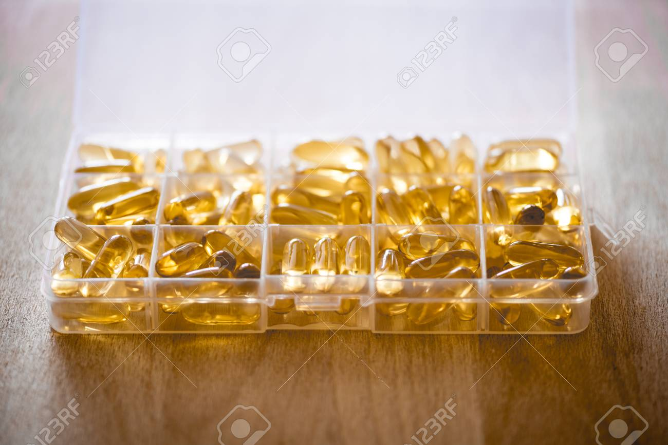Omega 3 6 9 Fish Oil Yellow Softgels Into Daily Pill Box On Wooden