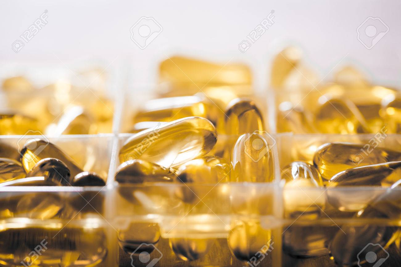 Omega 3 6 9 Fish Oil Yellow Softgels Into Daily Pill Box Backlit