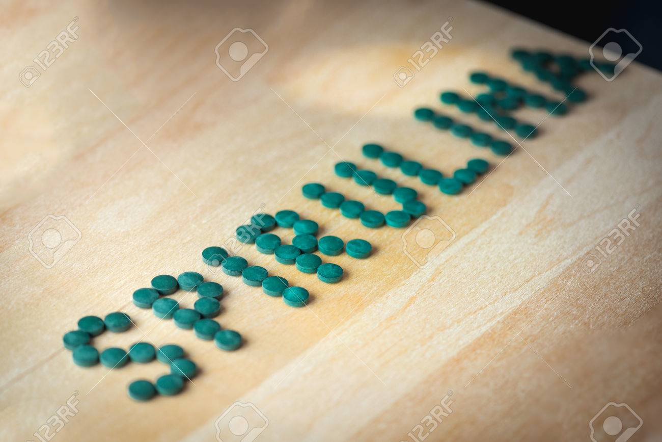 spirulina supplement pills making up the word spirulina on wooden