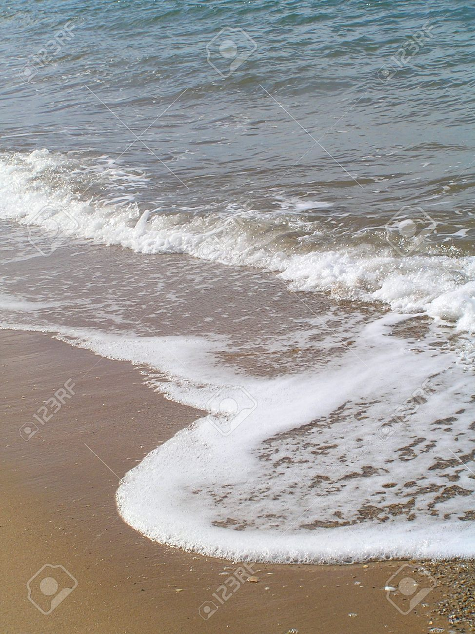 A small frothy sparkling ocean tide rolling in on the wet sand