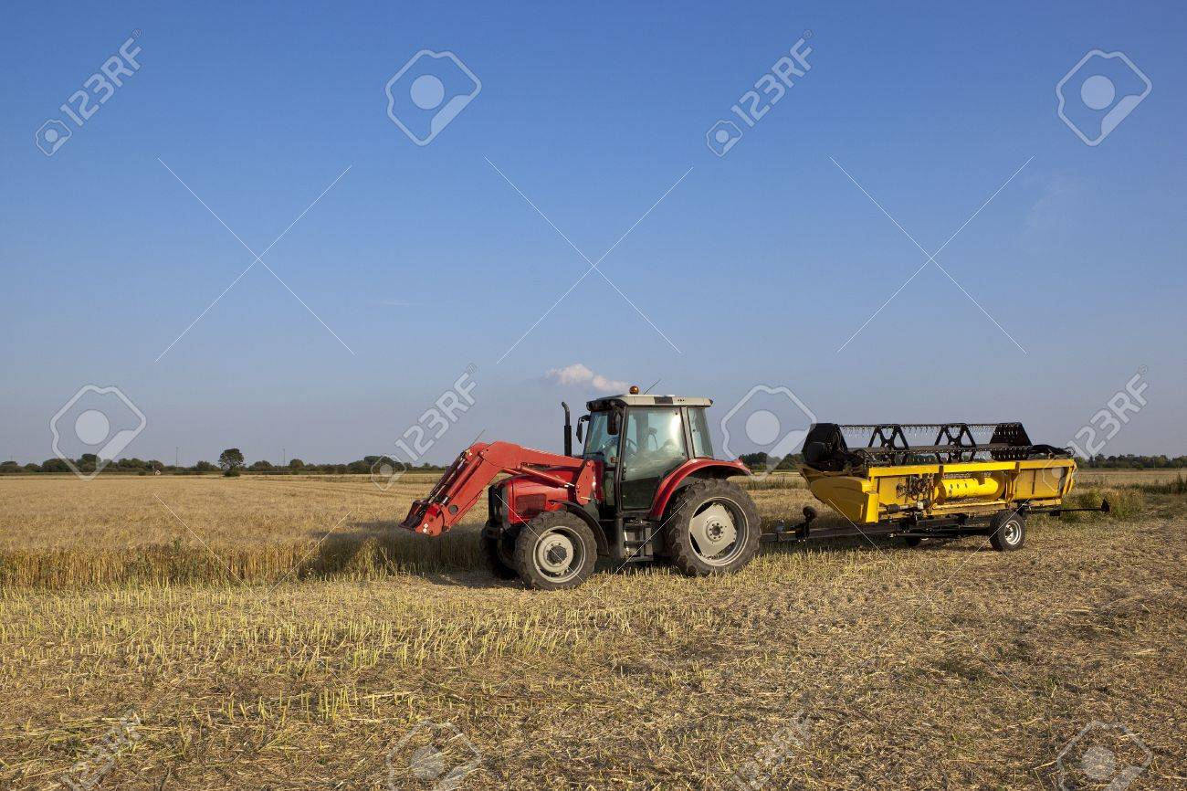 a red tractor with the cutting head of a combine harvester on