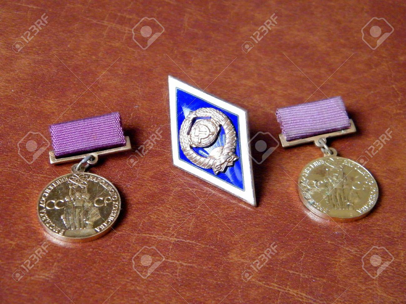 Two medals of Exhibition of Economic Achievements USSR and University badge (Soviet Union) on a brown background Stock Photo - 7475977