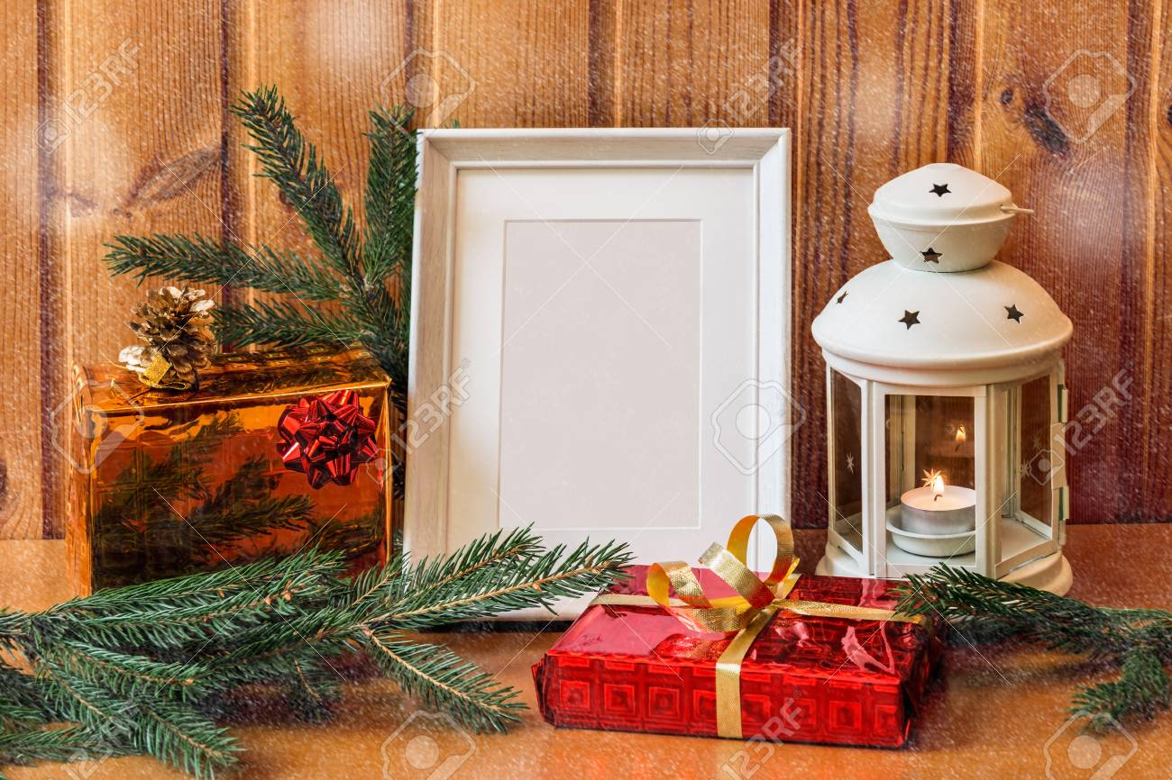 White Photo Frame, Lantern And Christmas Gifts On Wooden Table ...