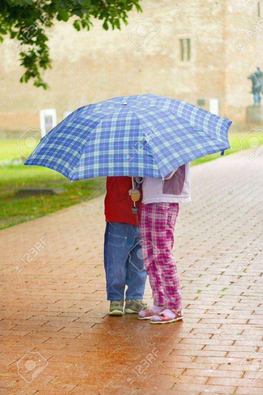 Young girl and boy under a blue umbrella in the rain Stock Photo - 7781548