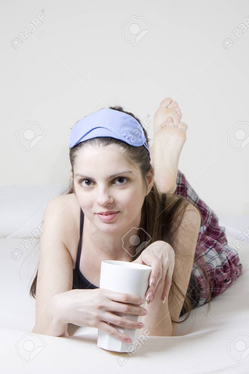 Young woman in the bed, with a cup of tea and blinkers in her head Stock Photo - 15492332