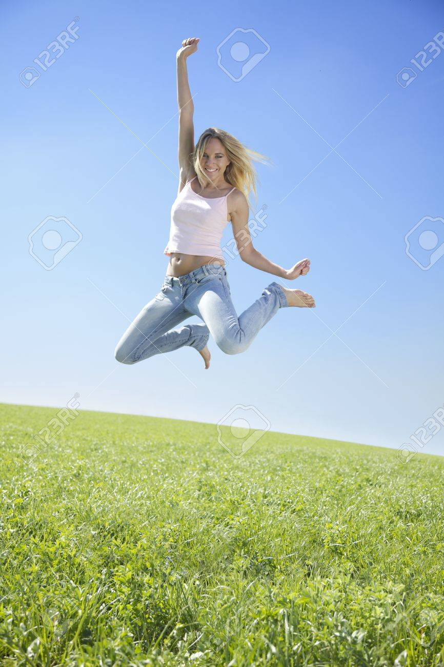 Jumping young woman enjoying sunshine in spring time Stock Photo - 10347016