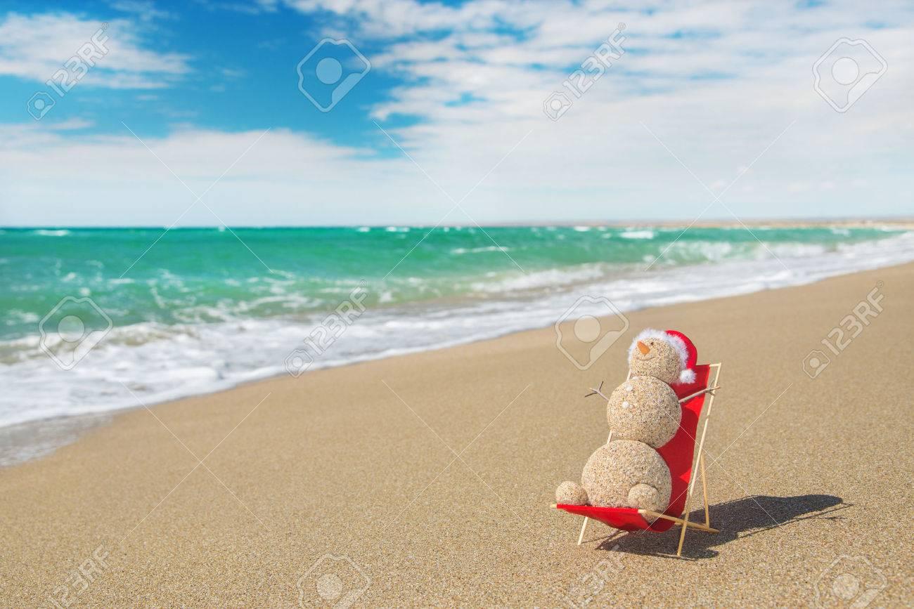 Sandy sneeuwman in rode kerstmuts zonnebaden op het strand lounge ...