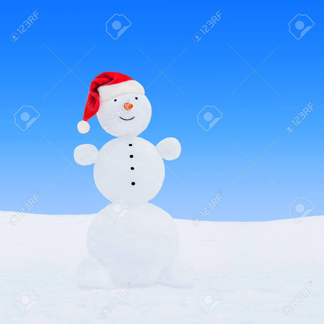 1a47605bf631d Stock Photo - Winter snowman in red Christmas Santa hat on snow at blue sky  background. New Year s greeting card concept