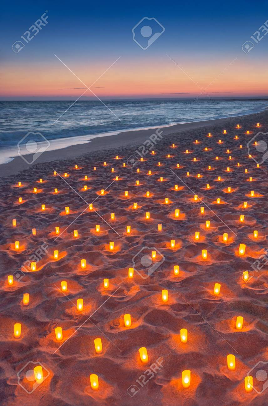 sunset ocean sandy beach decorated with lot flare lights of candles