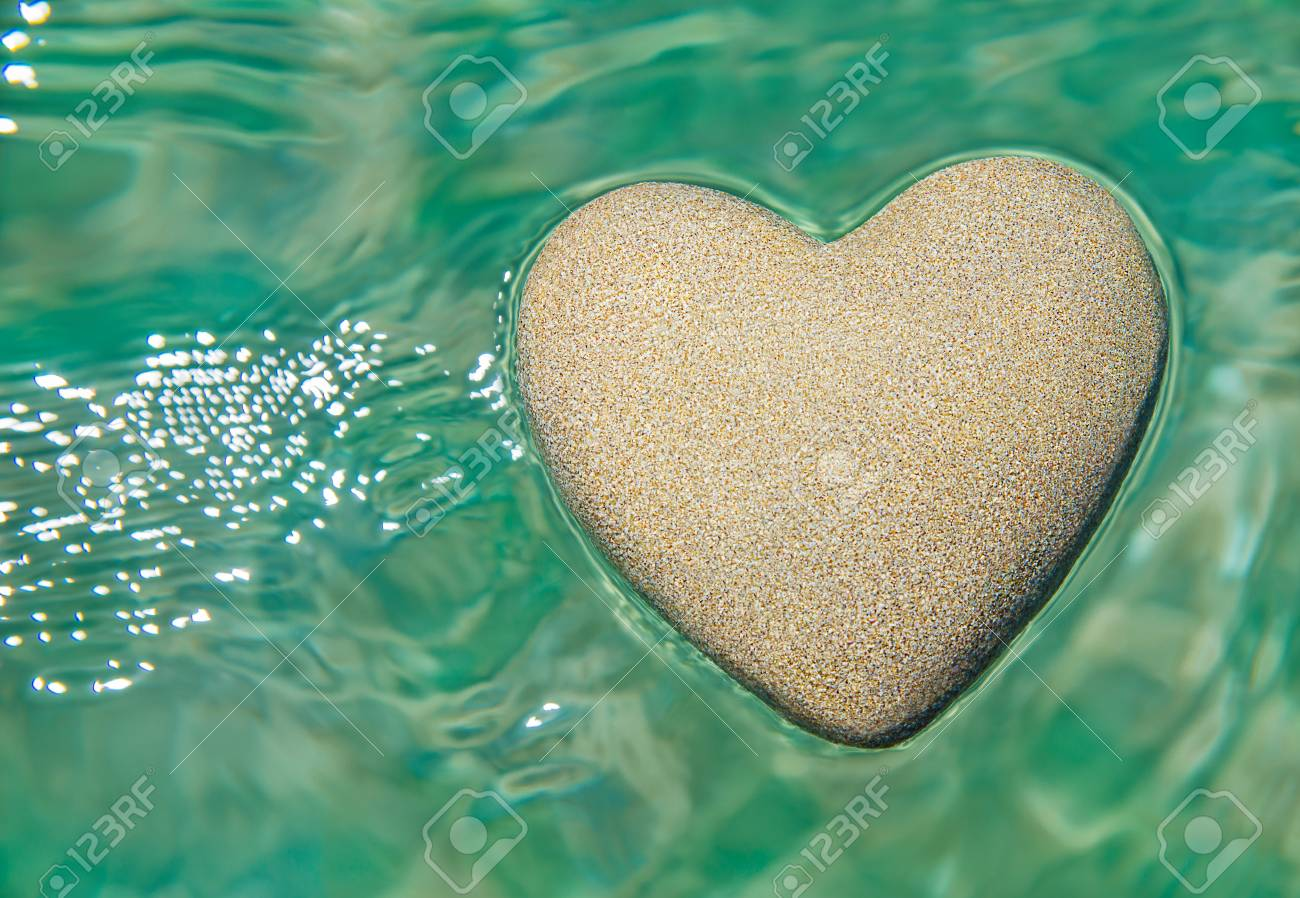 Heart Made Of Sand Floating In Transparent Turquoise Ocean Ripples