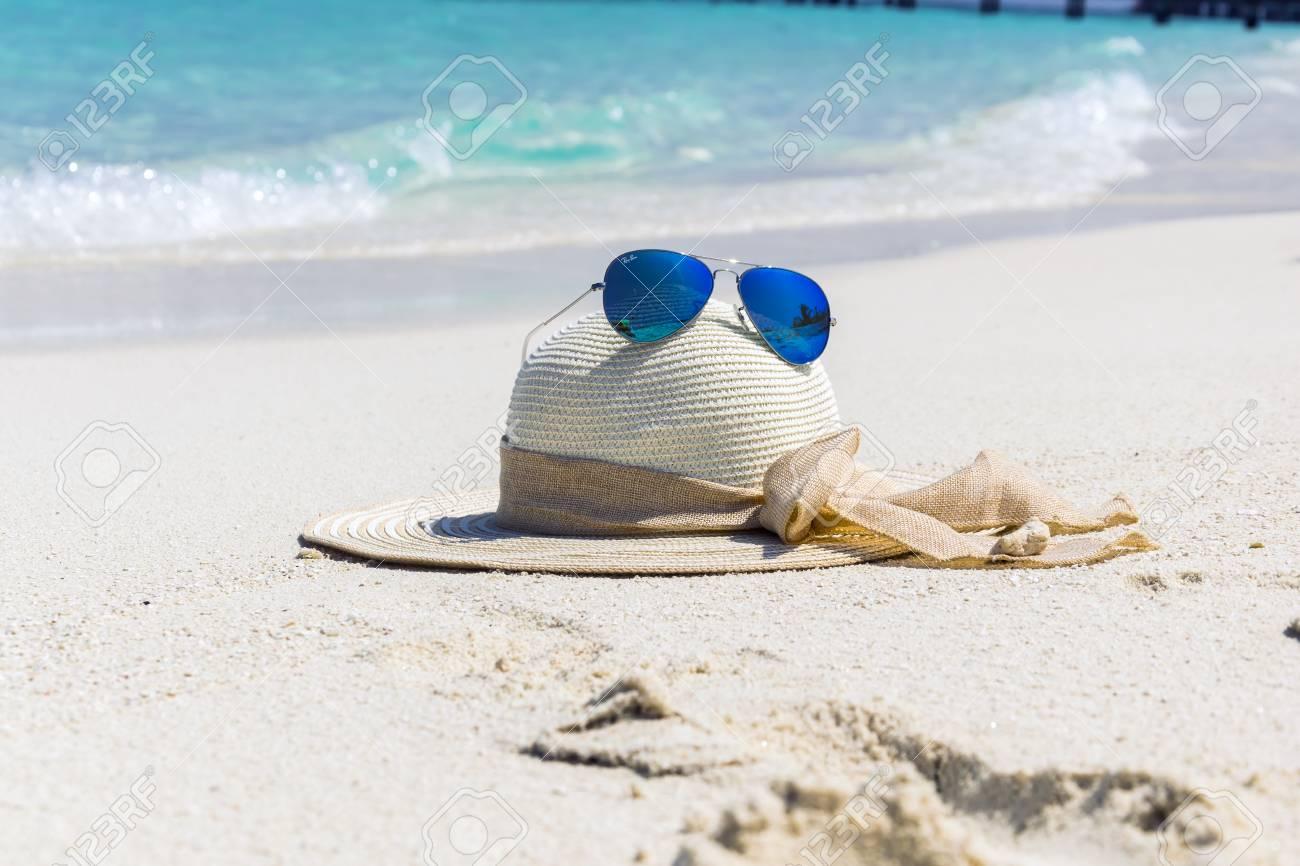 Chapeau De Femme Blanche Avec Des Lunettes De Soleil Aviateur Bleu Allongé Sur La Plage De Sable Blanc En Face De Locéan Turquoise