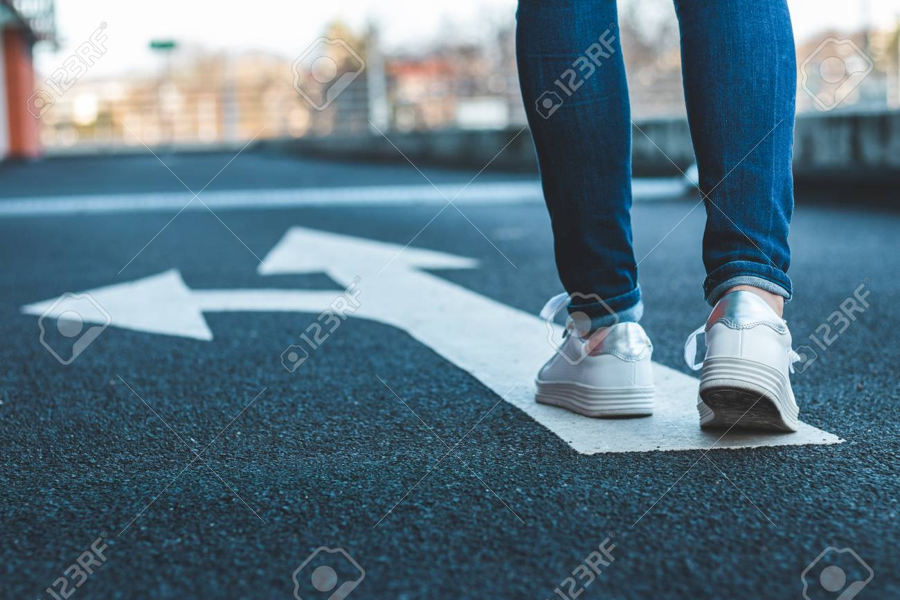 Make decision which way to go. Walking on directional sign on asphalt road. Female legs wearing jeans and white sneakers. - 120034490