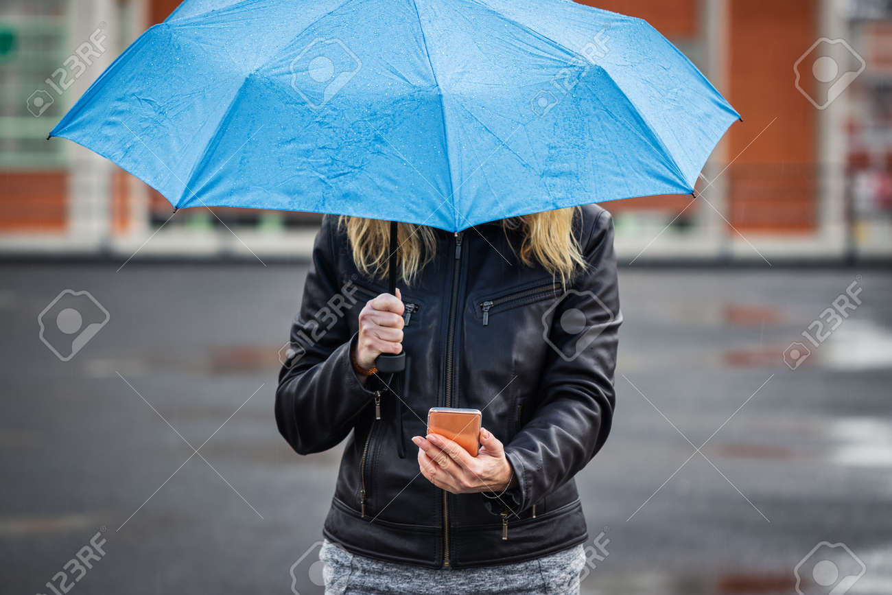 Woman with umbrella holding smartphone and standing in rain at street. Wireless internet connection on mobile phone in city - 148048172