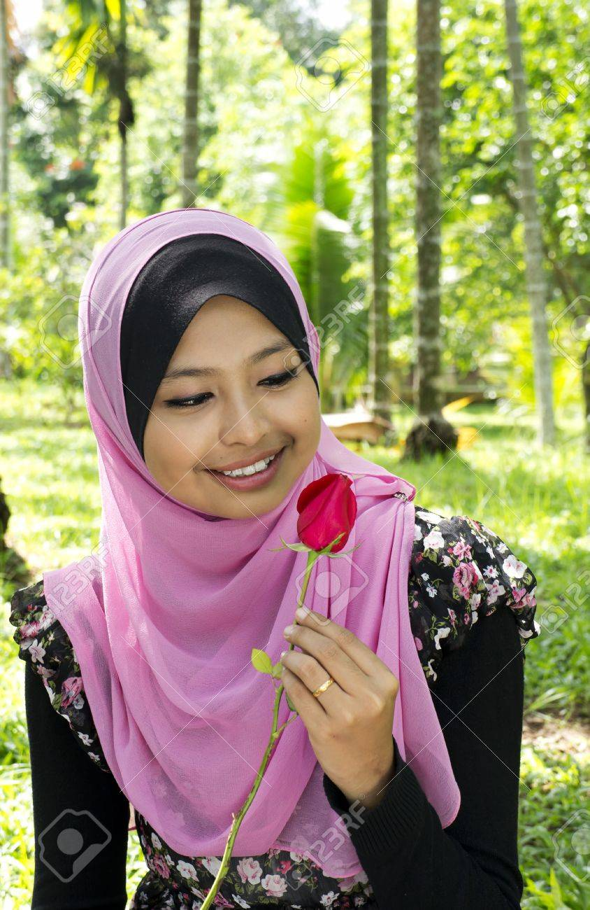 Close-up portrait of beautiful young Asian Muslim woman is holding rose flower Stock Photo - 11621608