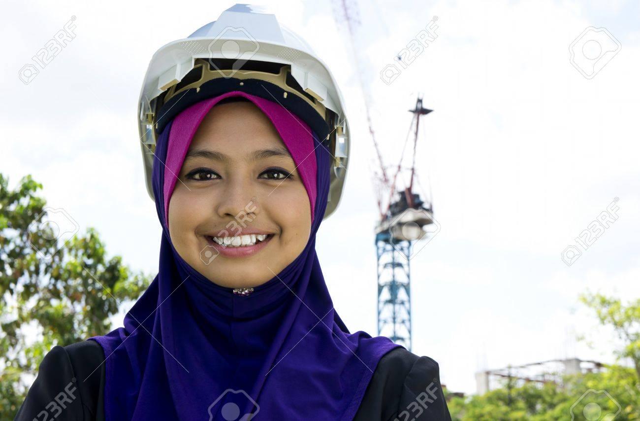 Portrait of young Muslim architect-woman wearing scarf with a protective helmet standing on the building background Stock Photo - 11621601