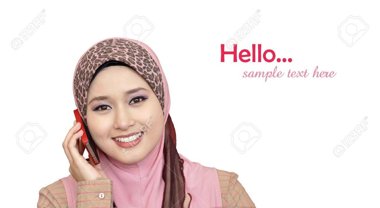 portrait of beautiful young Muslim woman using a mobile phone with a smile on a white background Stock Photo - 11621592