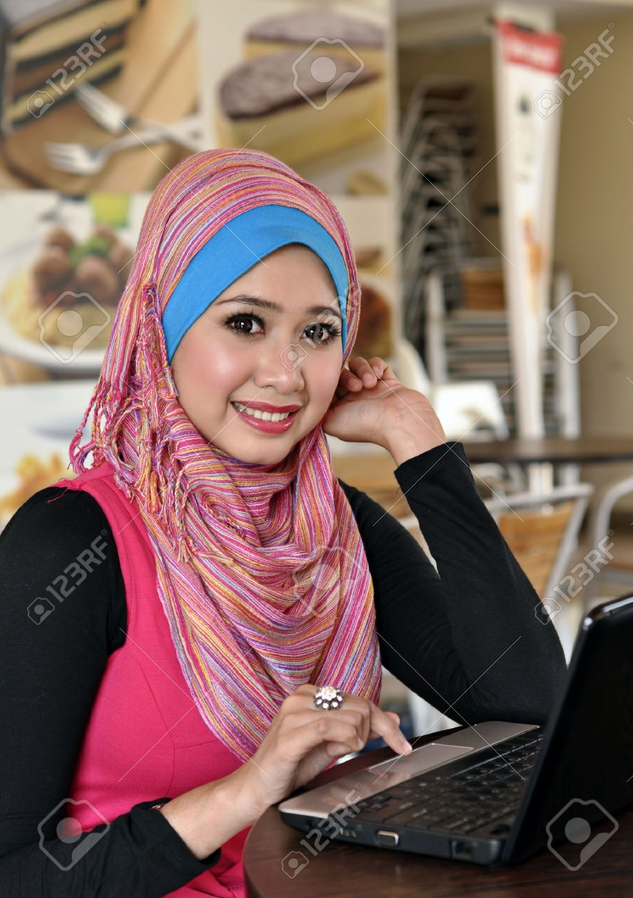 Pretty Muslim girl with laptop at cafe Stock Photo - 12898674
