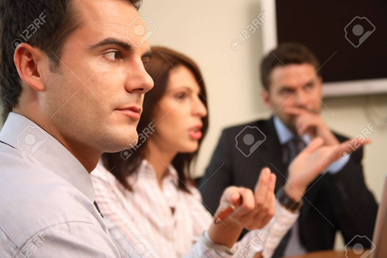 A group of four business people gather around a conference room table for a working discussion to plan a new project. Stock Photo - 1223370