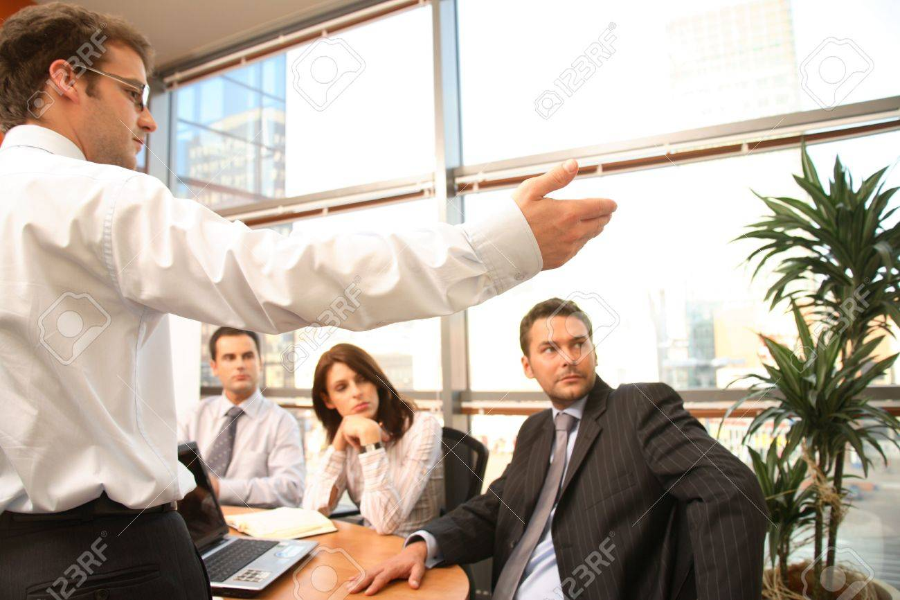 A group of four business people gather around a conference room table for a working discussion to plan a new project. Stock Photo - 1223376
