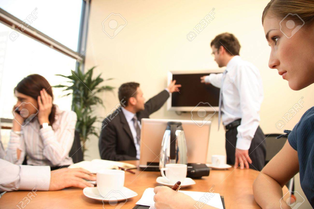 group of four business people at work. one woman is calling on a phone,another is making notes,two men are talking about data at tv screen. Stock Photo - 1405559