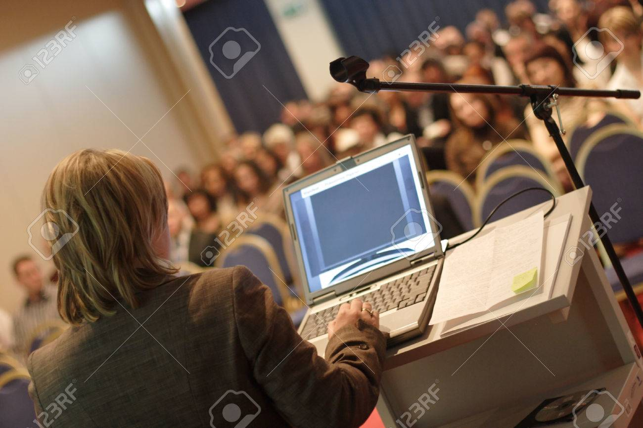 Business woman at podium with laptop computer lecturing audience in auditorium Stock Photo - 1582916