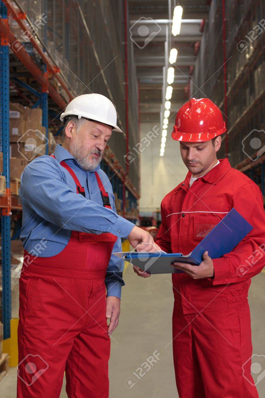 two workers in uniforms in warehouse reviewing project Stock Photo - 3232342