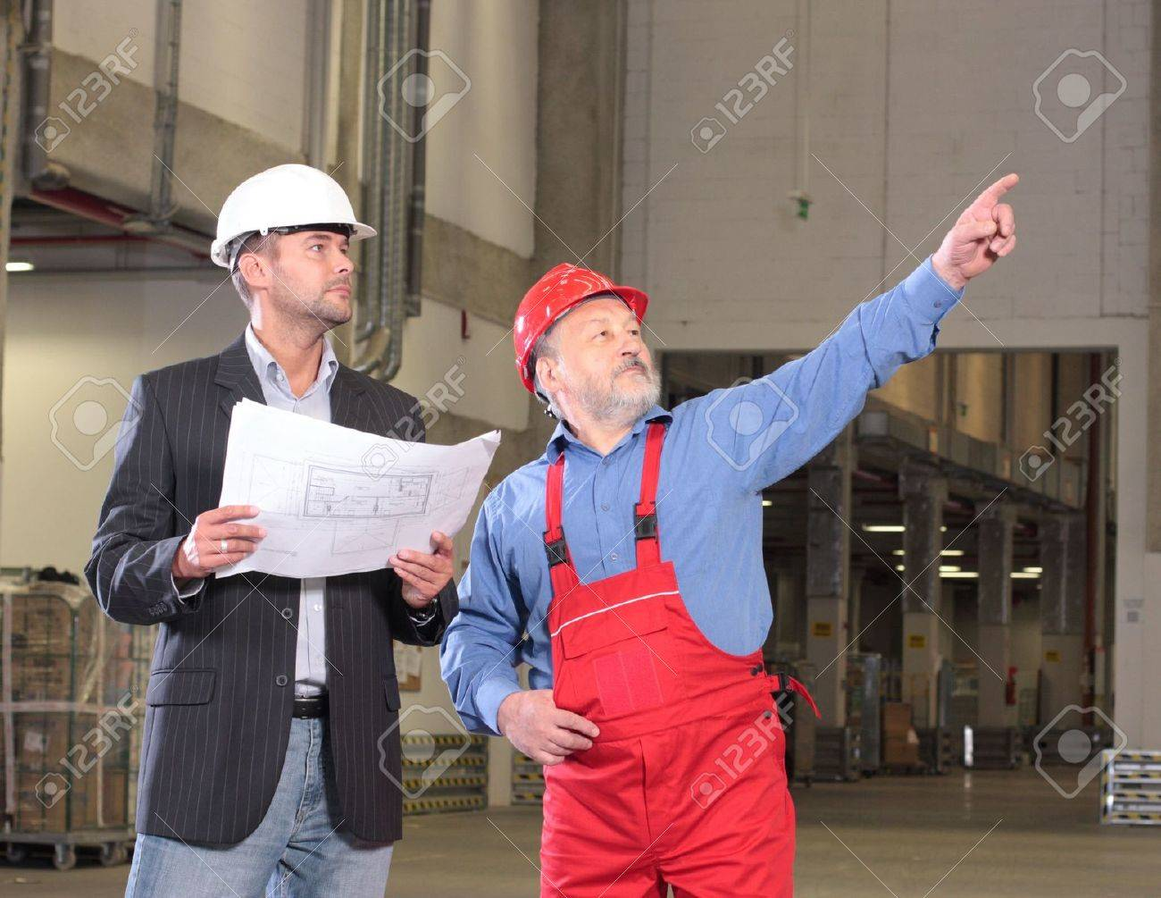 businessmen and older worker, wearing hardhats looking at a set of blueprints and discussing a construction project. Stock Photo - 3246535