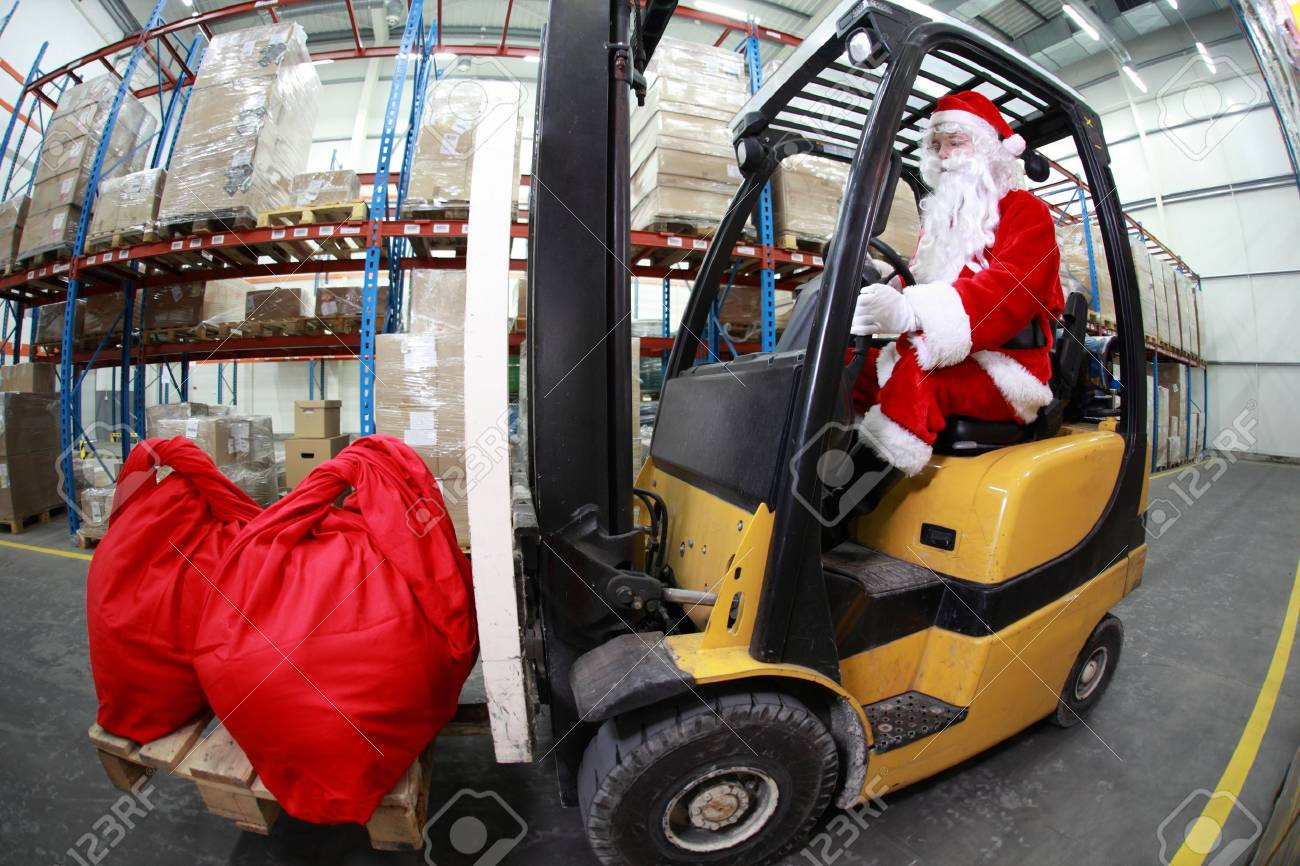 Santa Claus As A Forklift Operator At Work In Warehouse. 2 Large ...