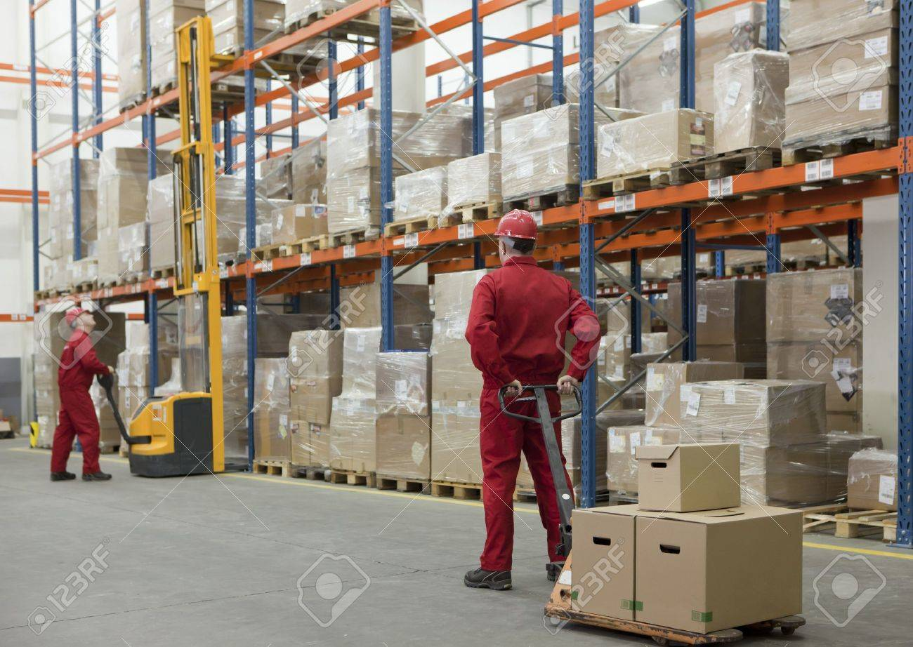 Two workers in uniforms and safety helmets working in storehouse Stock Photo - 9801899
