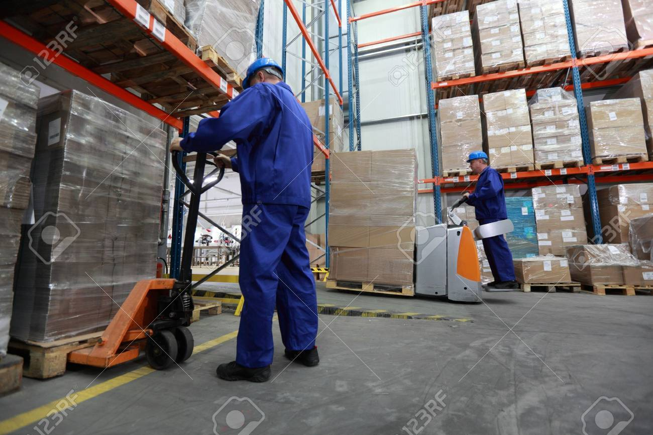 Two workers in uniforms and safety helmets working in storehouse Stock Photo - 10695273