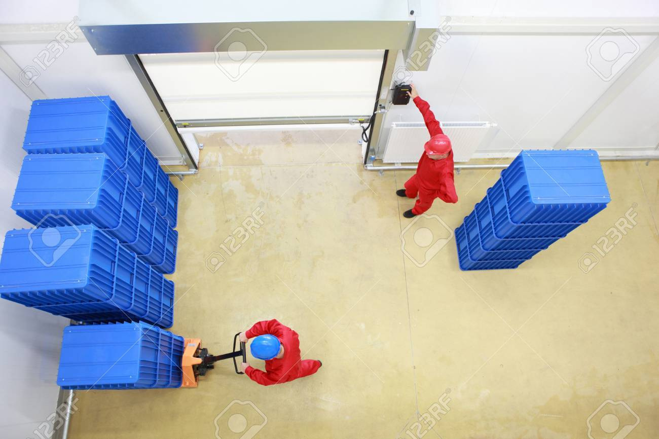 Overhead view of two workers. one is opening a gate another is loading plastic boxes in small warehouse Stock Photo - 13234237