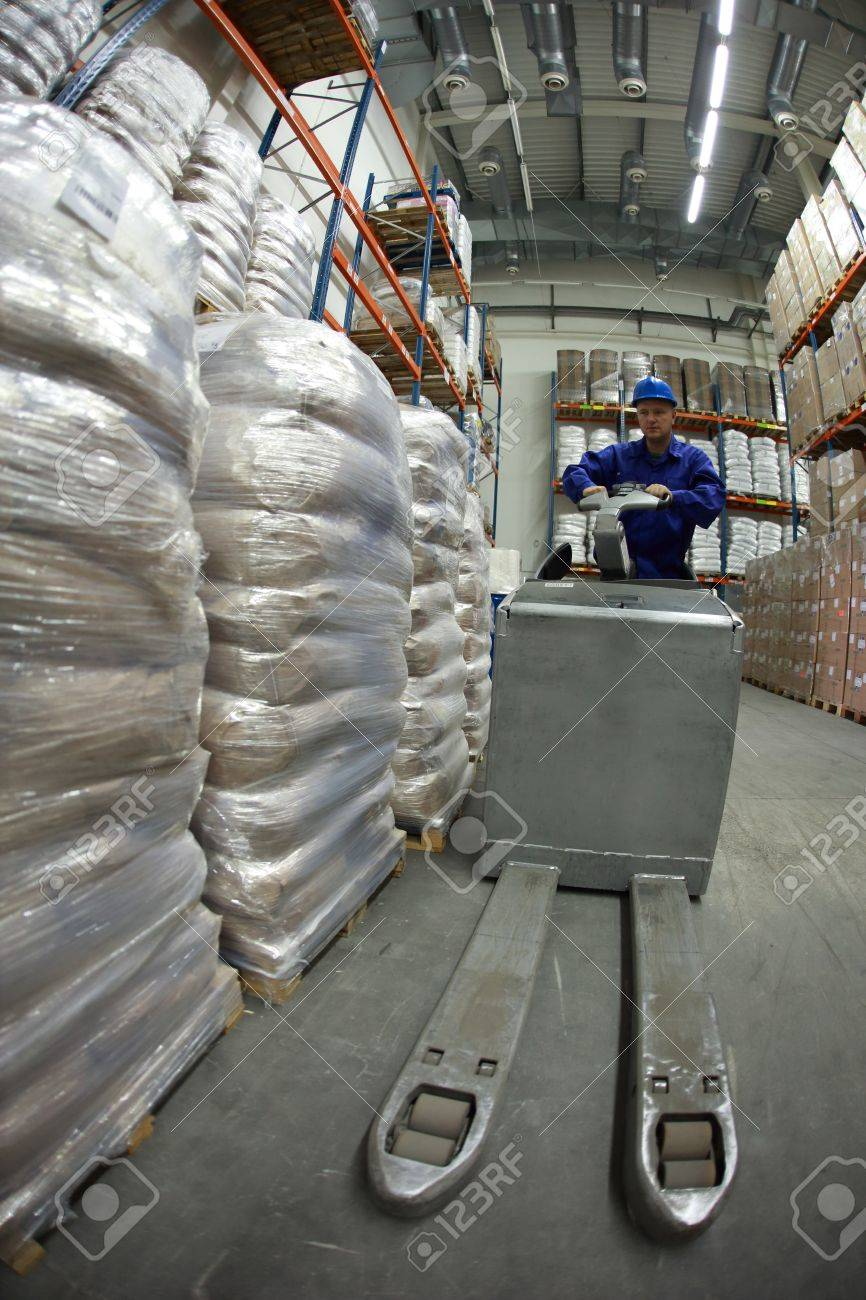Forklift operator in blue uniform and  helmet at work in warehouse Stock Photo - 14412550