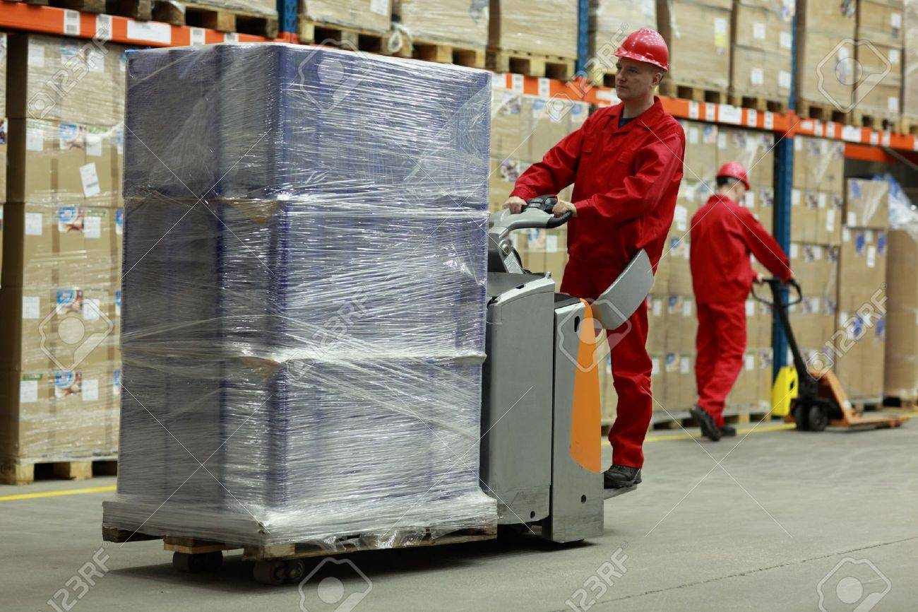 Two workers in uniforms and safety helmets working in storehouse Stock Photo - 14526372