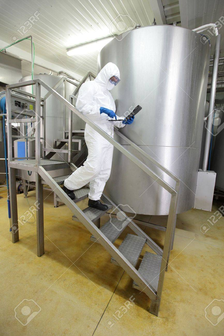technician in white uniform focused on tablet, walking down the stairs in industrial process interior Stock Photo - 15262494