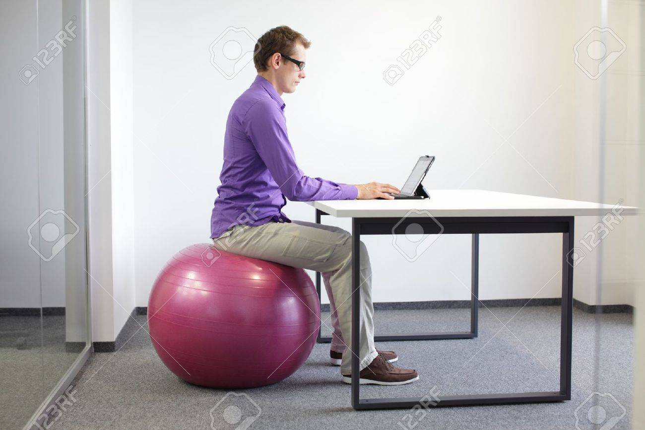 man on stability ball working with tablet - correct sitting position at workstation Stock Photo - 21824090