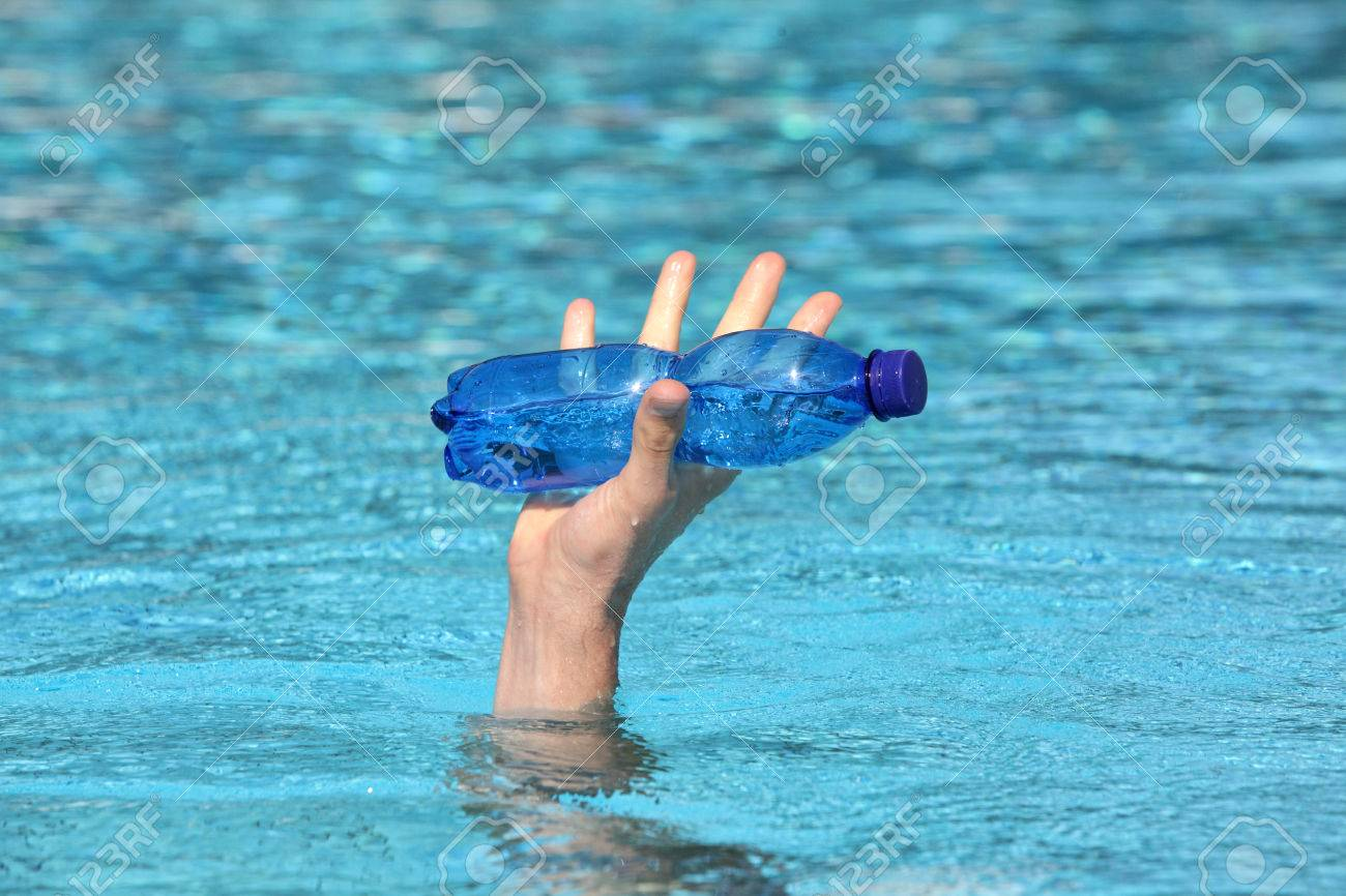 hand raising out of water holding plastic blue bottle of water Stock Photo - 24967484