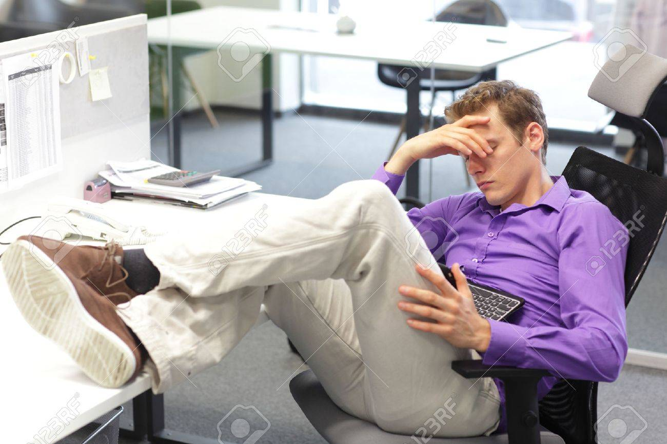 Young businessman snoozing over his tablet in office - 27574577