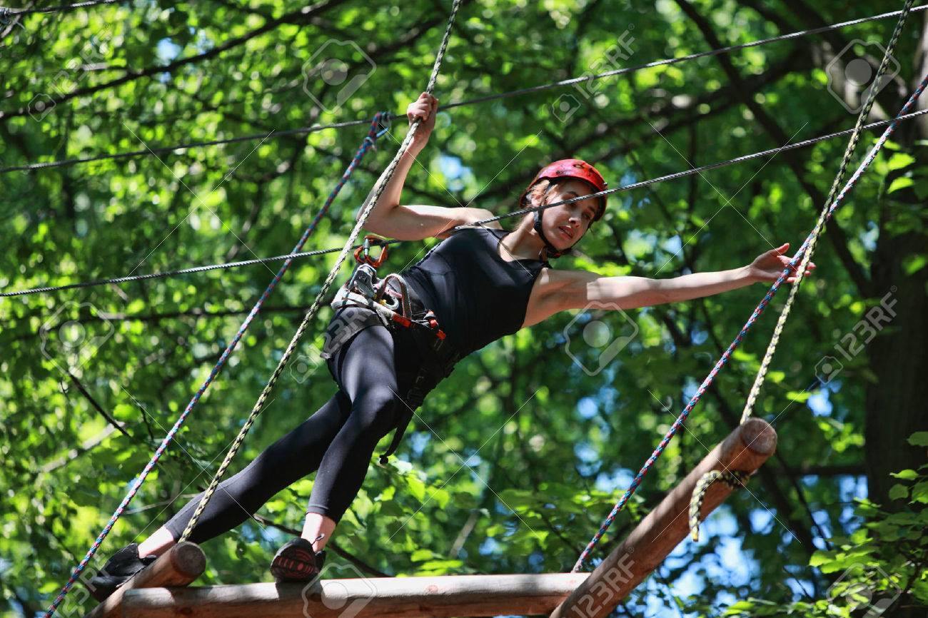 Young caucasian attractive woman climbing in adventure rope park in mountain helmet and safety equipment - 28069830