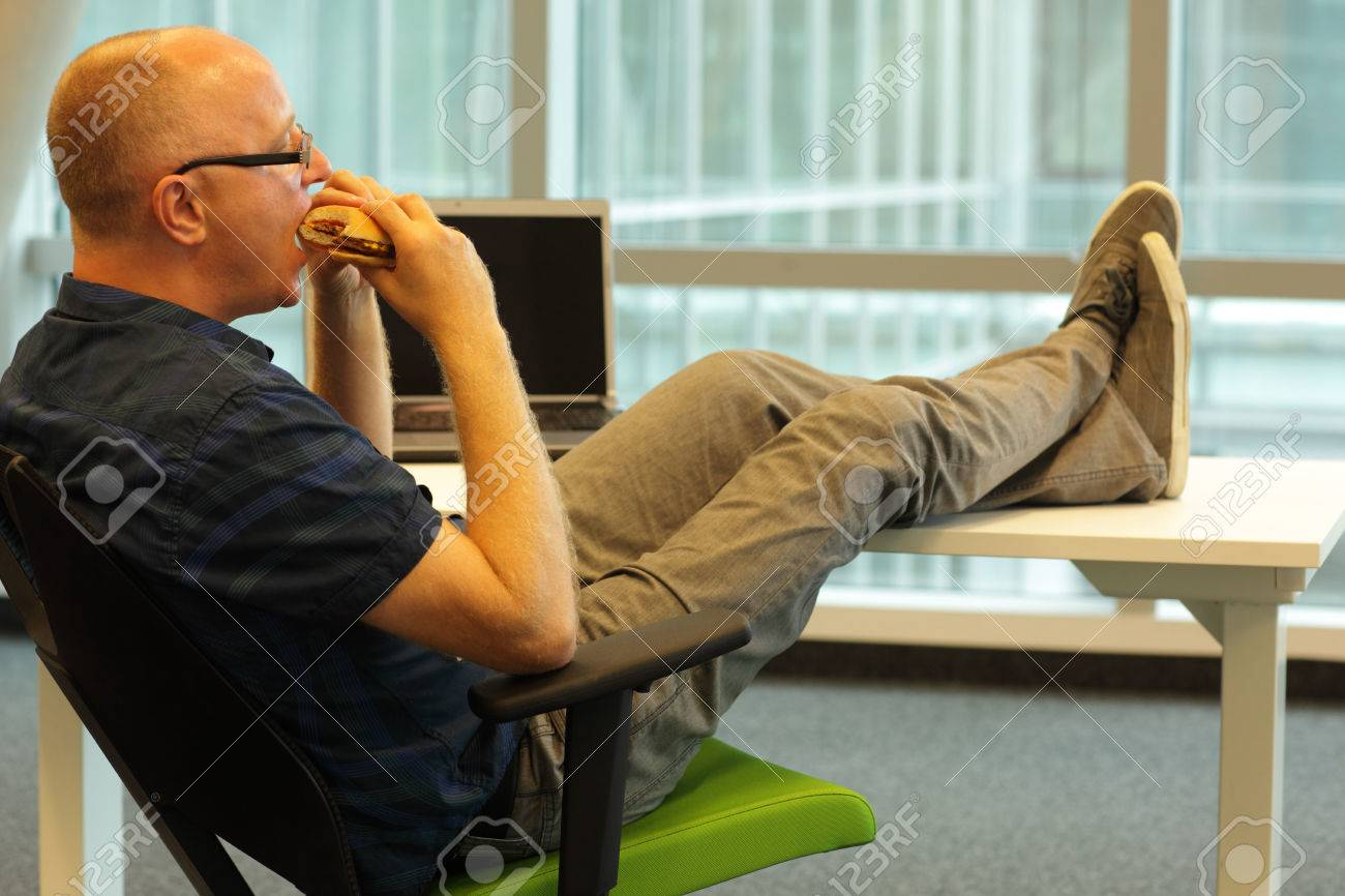 middle aged caucasian man sitting in relaxed position at the desk, eating hamburger in his office - 32612694
