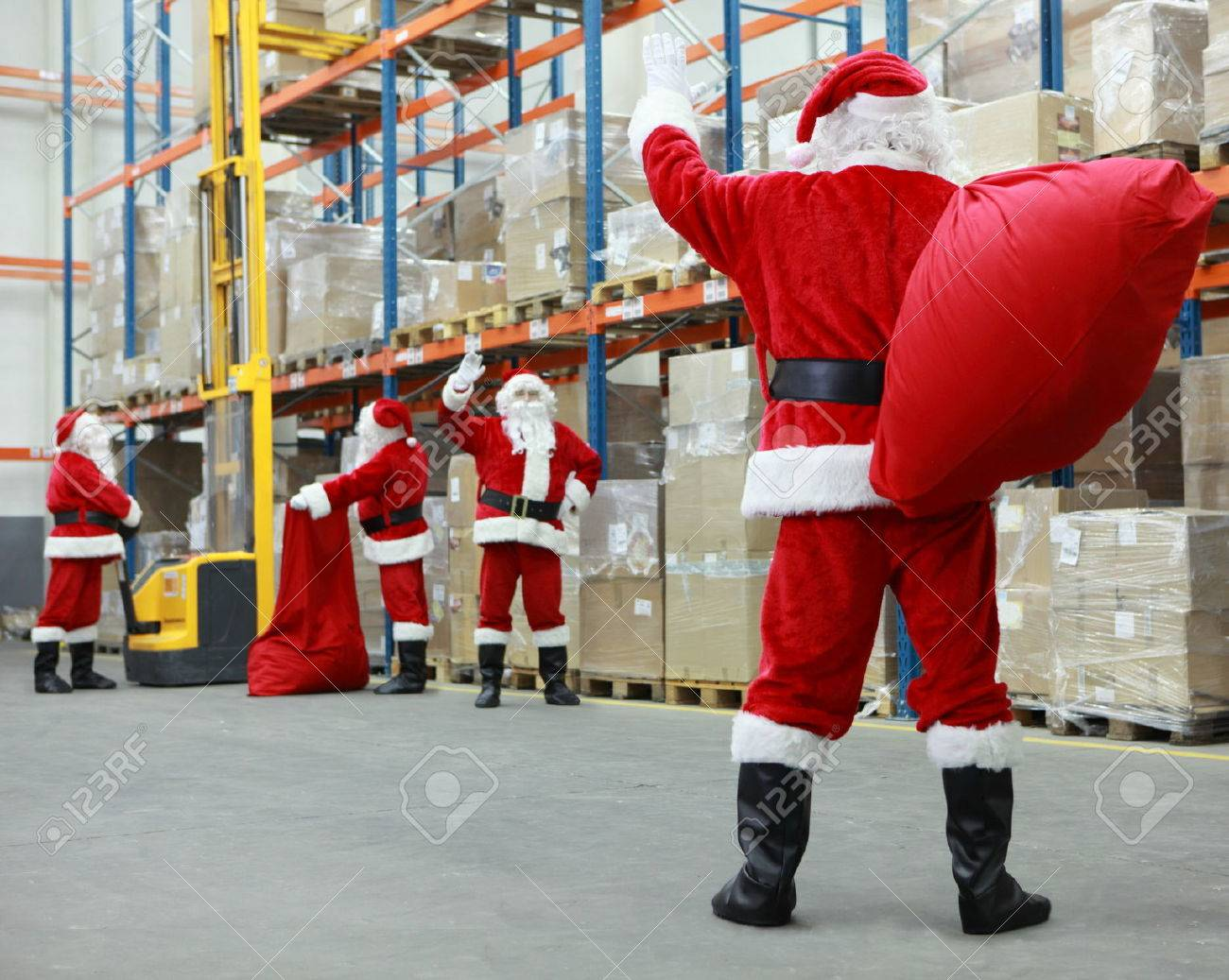 Group of santa clauses working together in storehouse with gifts - 33313525